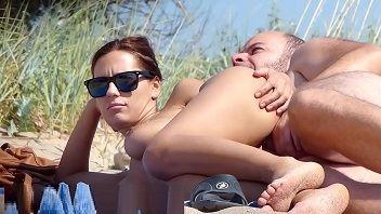 Tacando a rola discretamente na esposa putinha na praia de nudismo